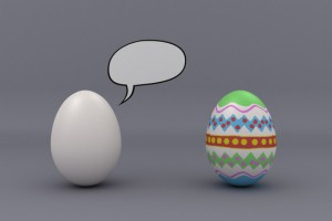 Two eggs in studio setting with speech bubble. One egg is blank and the other one is painted.